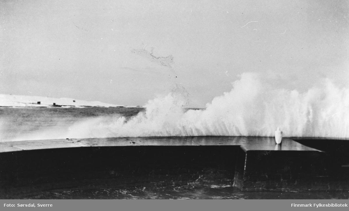 Bildet av bølger som bryter over moloen.