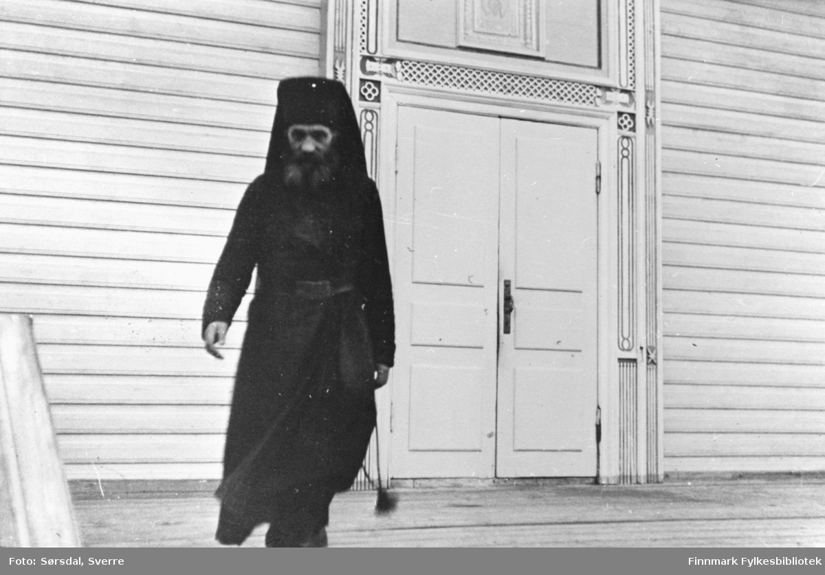 Bildet av presten på kirketrappa til Petsamo kirke. Man ser en del utskjæringer rundt døra.
