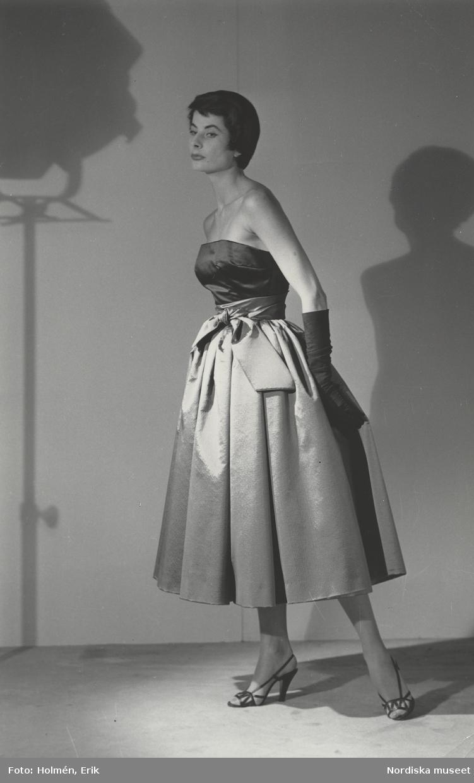 c98639a163d Modell i axelbandslös aftonklänning med band i midjan, livet i svart  duchesse och kjolen i