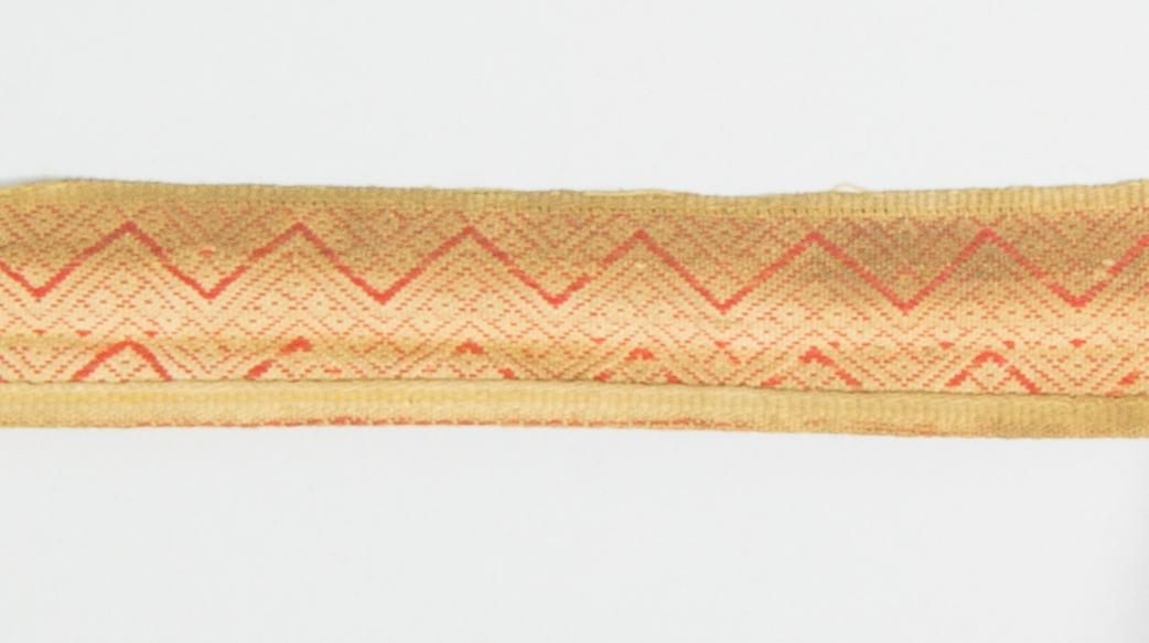 Kjolsäck till dräkt för kvinna från Mora socken, Dalarna. Modell med avskuret framstycke. Tillverkad av brunt skinn med dekor på framstycket och överstycket av remsor med stansat mönster av skinn, med underlägg av rött kläde som lyser genom, underläggssöm. På framstyckets band även en kant av grönt vadmal, nästan helt bortnött. Inlägg i sid- och bottensöm av två remsor tyg, rött kläde och grön vadmal. Mönstervävt band med plockat mönster i rött ullgarn på vit botten av lin eller bomull, gula kanter.