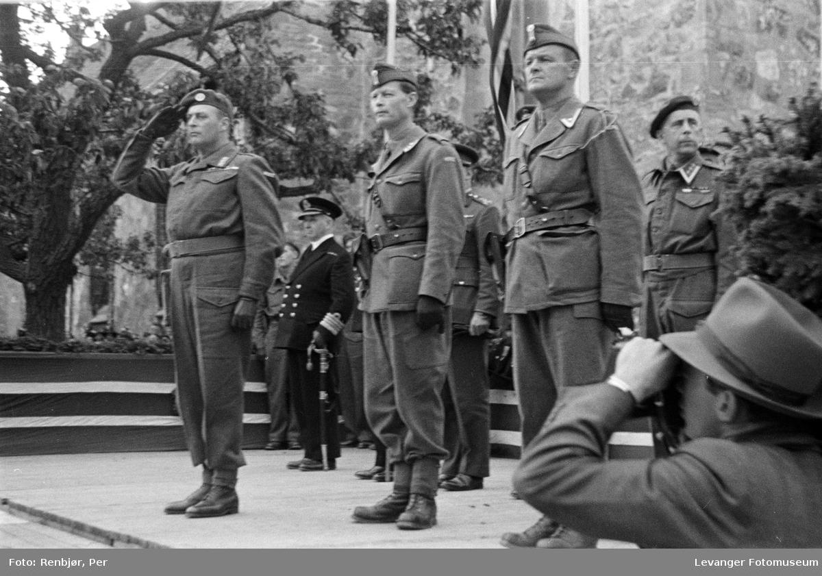 Kronprinsen salutterer soldatene på tribunen.