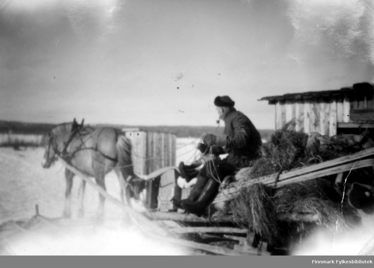 Fotografi av Magnus Stenbakk på vei til skogen. På bildet ser vi en hest som trekker sleden hvor Magnus sitter og holder tømmene. Han er kledt i jakke, lue og mørke bukser. Støvlene har høyt skaft. I munnen har han en pipe. Til høyre i bildet ser man en trebygning. På sleden ligger det høy og materialer