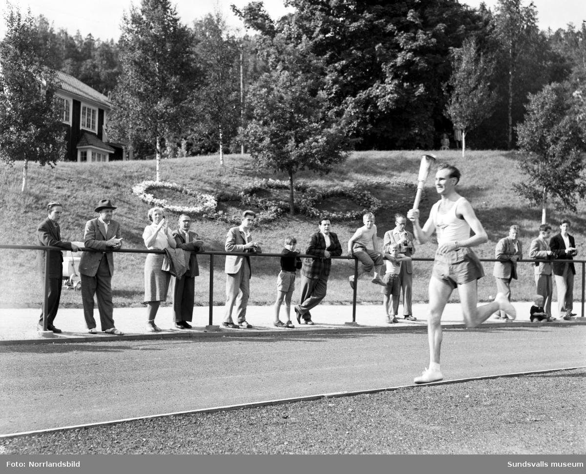 Den olympiska elden passerar Sundsvall inför sommarspelen i Helsingfors 1952 med högtidlig stafettväxling i Idrottsparken. In på arenan förs facklan av IFK-löparen Eric Nilsson, som är uttagen till Olympiaden på 3000 meter hinder. Därefter tar SAIK-brottaren och OS-silvermedaljören från 1936, John Nyman över för att påbörja facklans färd vidare mot Härnösand och Kramfors.