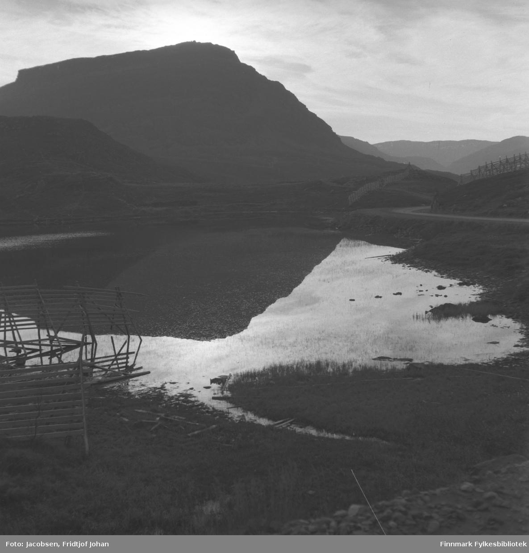 Et blikkstille Jansvann med fjellet Tyven i bakgrunnen, fotografert en sommerdag. Rv94 ses til høyre på bildet.