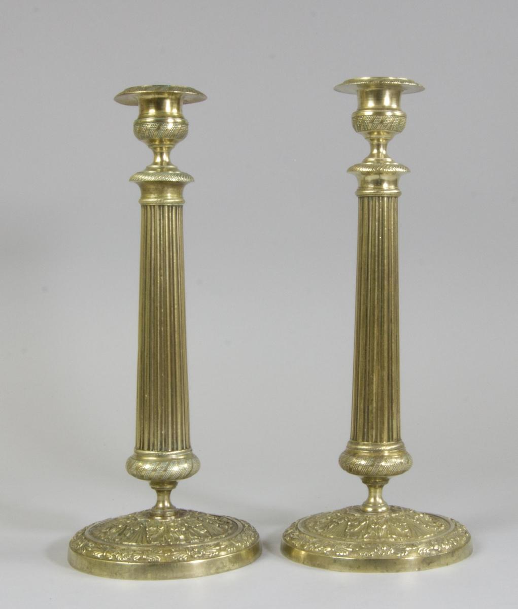 Ett par ljusstakar av brons. Manschetter med räfflor och med bronserade urnformade ljuspipor. Räfflade patinerade och kolonnformade skaft. Runda fotplattor med akantusblad.