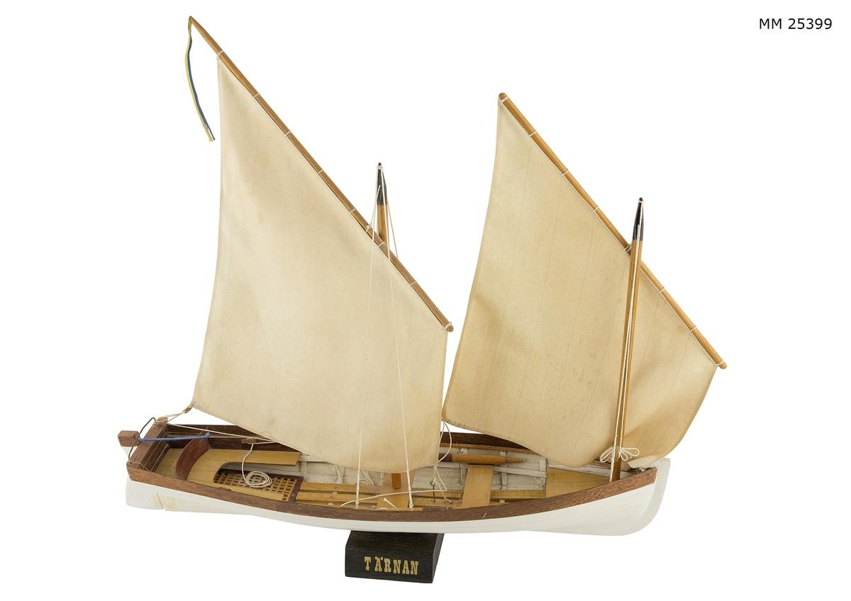 """Barkass med vitmålat skrov och naturfärgad, fernissad reling och översta bordläggningsplanka. Båten har två master med loggertsegel på varje mast. Den förliga masten något kortare än den aktra dito. I båten ligger en åra på varje sida lagd över tofterna. Roder i aktern med roderpinne som är lindad med blå tråd.   Modellen står på en mindre mörkbrun träbricka. Brickan är märkt med bokstäver i guld/gult: """"TÄRNAN"""".  Text på papperslapp på brickans undersida: """"Tärnan b. som låringsbåt t. fregatt. Vanadis 1861, Modellen b. i Karlskrona -1984- av Nils Ovander""""."""