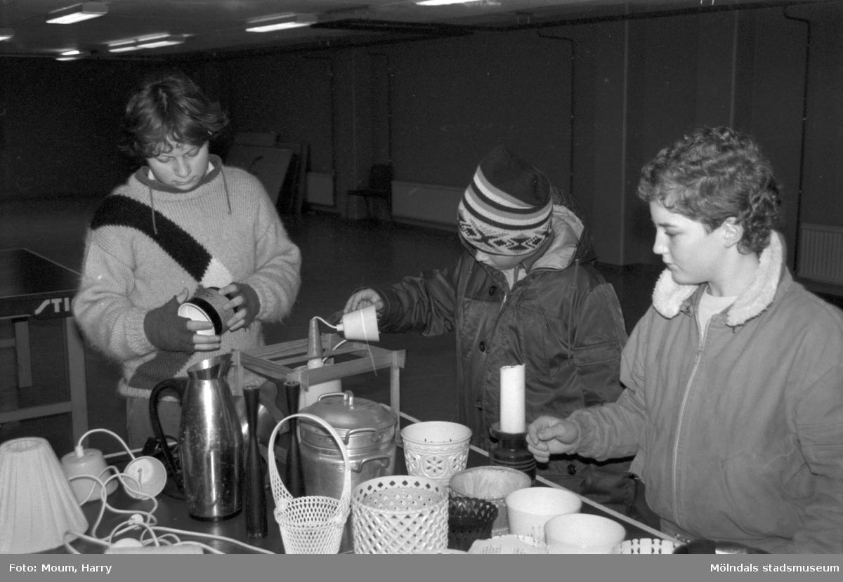 """Loppmarknad på Almåshallen i Lindome, år 1985. """"Loppis är kul tyckte Tom och Magnus Andersson samt Bo Gunnar Bergman.""""  För mer information om bilden se under tilläggsinformation."""
