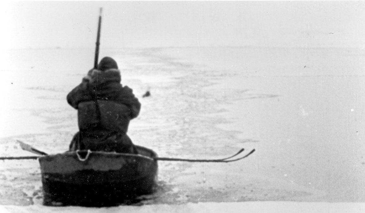Portrett, en person i en liten båt i ei råk i isen.