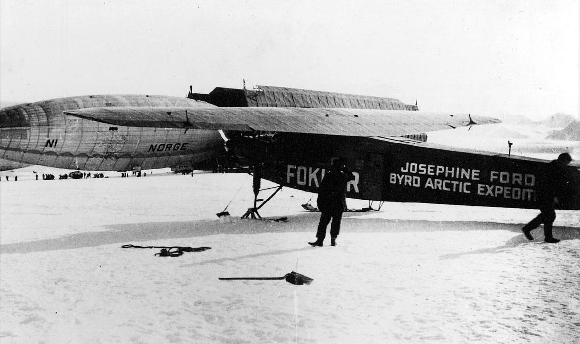 """1 fly på bakken, Fokker, med påskrift """"Josephine Ford Byrd Arctic Ekspedition"""". Luftskipet Norge bak. Mange personer i området. Snø på bakken."""