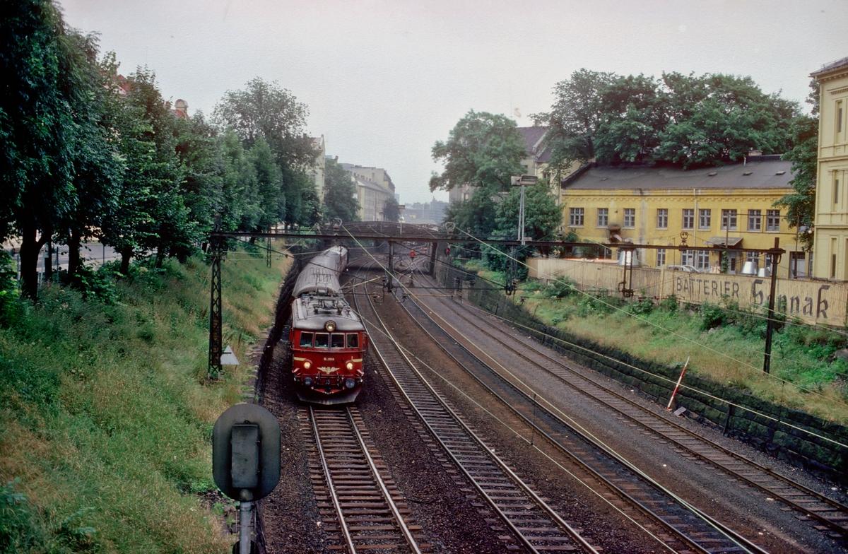 """NSB persontog til Vestfoldbanen kjører ut av """"Strupen"""" fra Oslo V. Lokomotiv El 11 2108. Bildet er tatt fra Munkedamsveiens bro over Drammenbanen, og forbindelsessporene til Filipstad. Reklame fra Sønnak på gjerdet til høyre."""