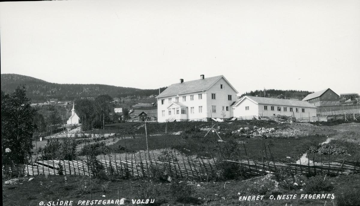 Prestegården i framgrunnen til høyre, og kirka i til venstre, Volbu