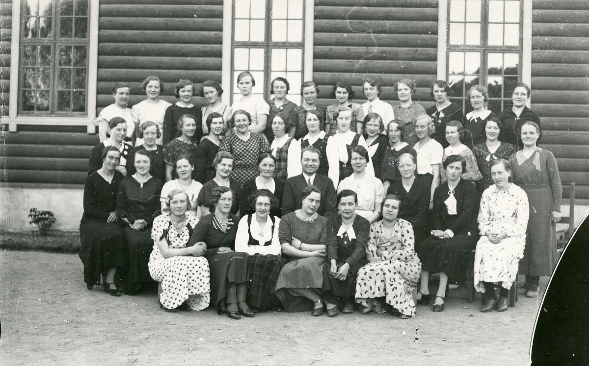"""Kvinner oppstilt foran husvegg. """"Vårkurset 1936"""""""
