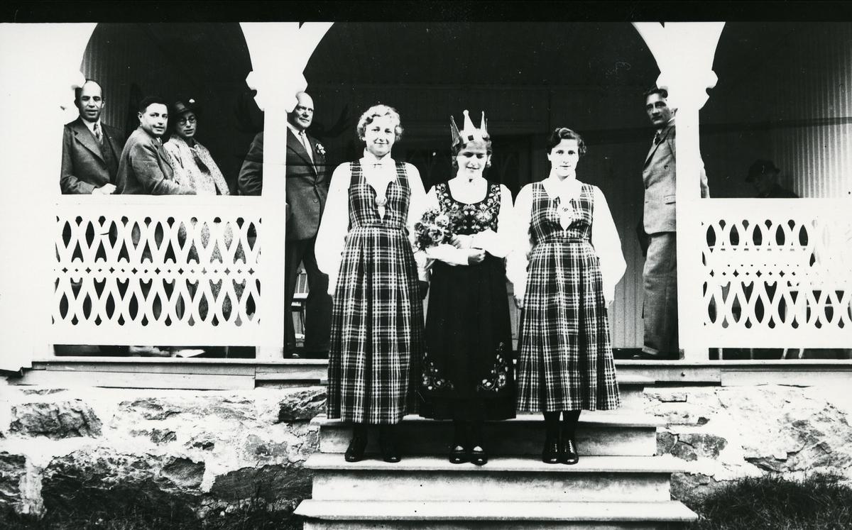 Tre kvinner i bunad på trapp foran inngangsparti, fru Lappen til venstre, menn bak. Kåring av Valdresprinsessa