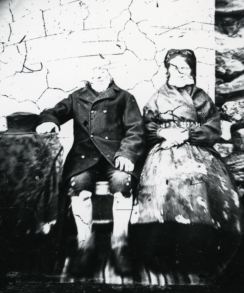Mann og kvinne sittende ved bord, kledd i tradisjonelle folkedrakter. Hatt liggende på bordet. Helge og Guri Ellingbø