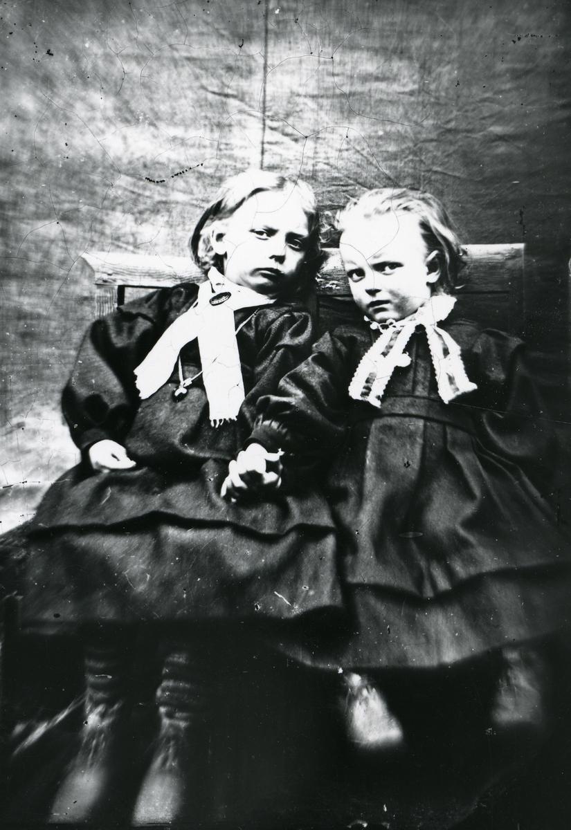 To barn i kjoler, sittende på stol