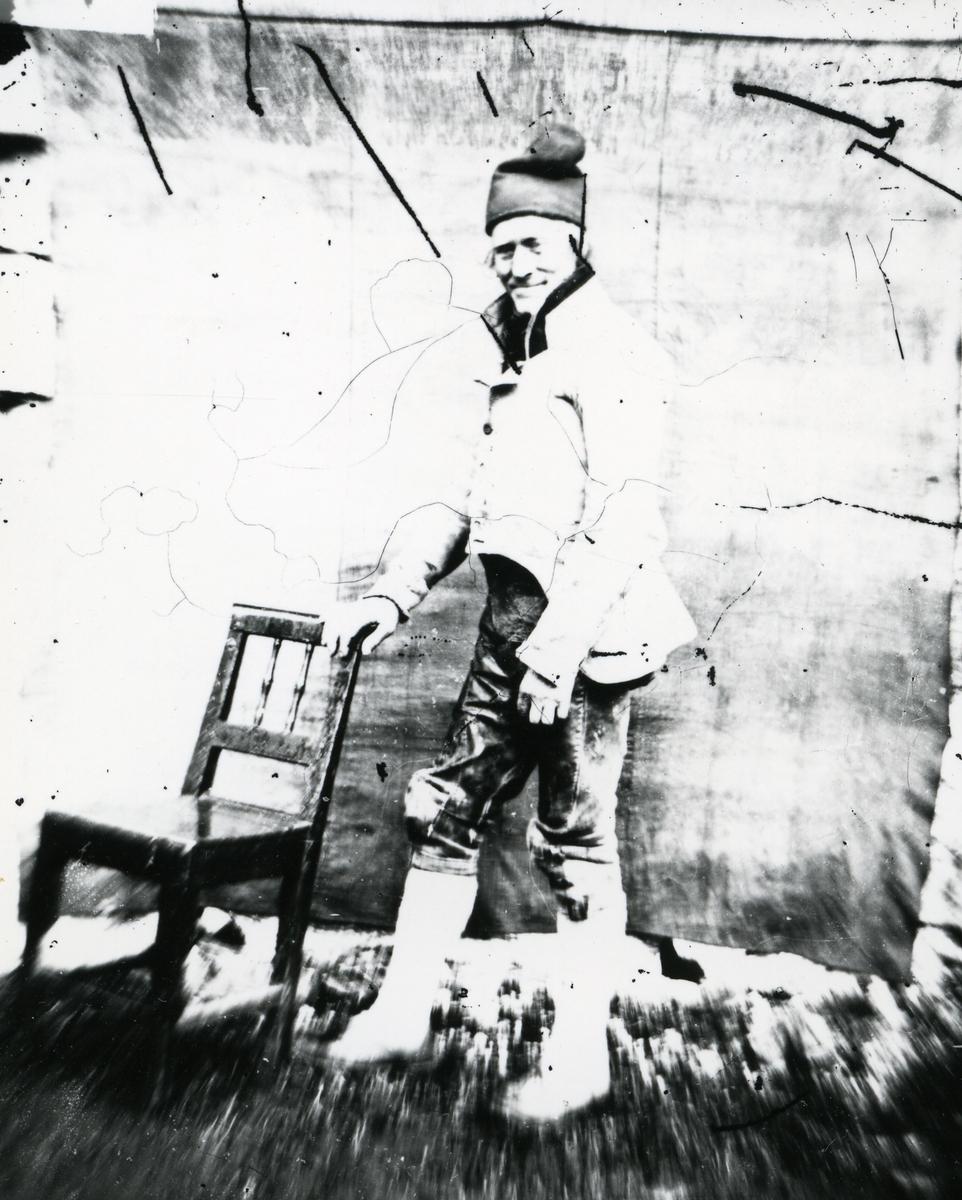 Mann kledd i tradisjonelle klær, blant annet lys trøye, kort bukse og topplue, stående ved stol foran lerret