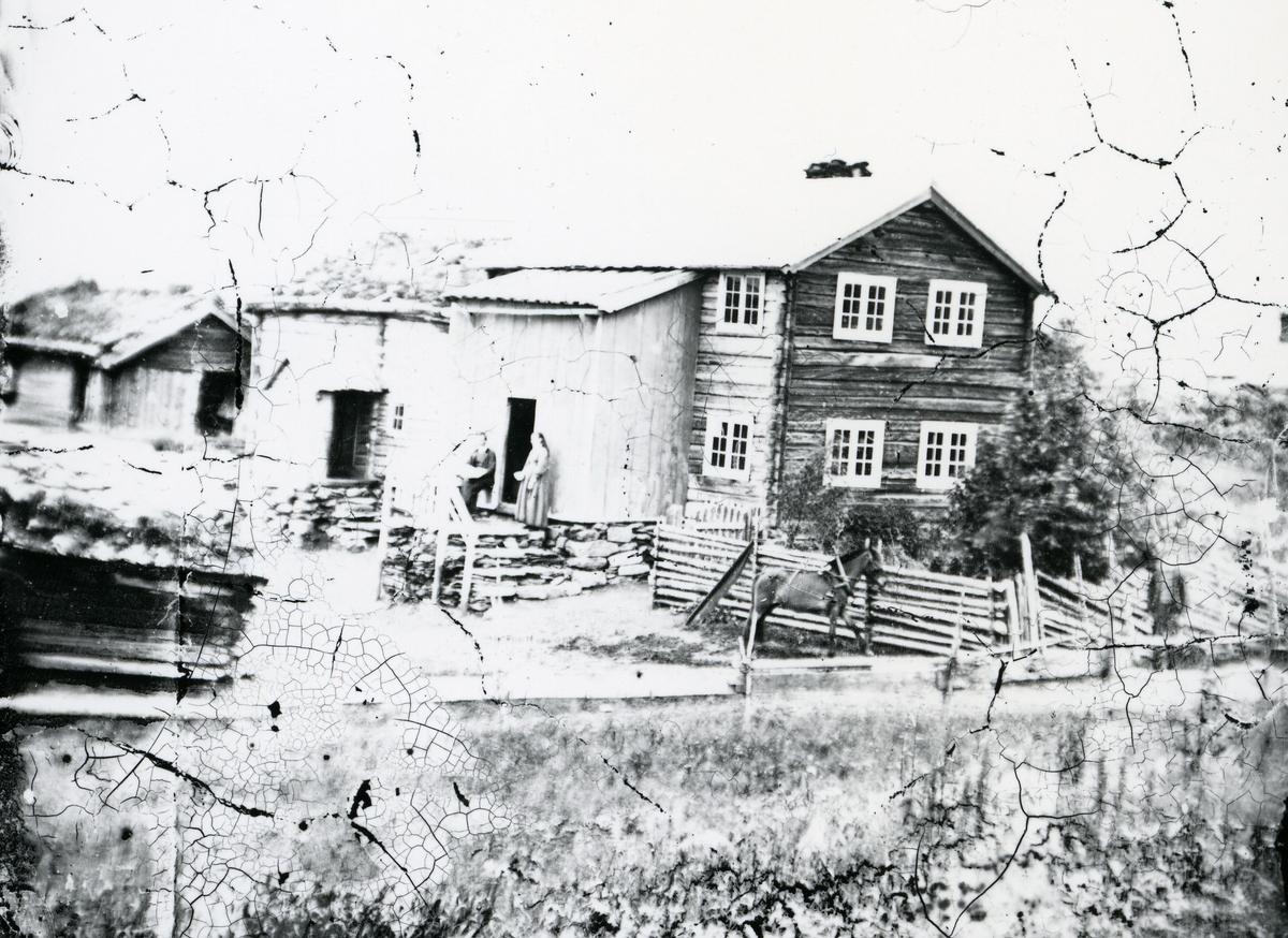 Gårdstun med bygninger, blant annet toetasjes hovedbygning. Mann og kvinne foran inngangen, hest ved gjerdet, mann foran gjerdet til høyre i bildet