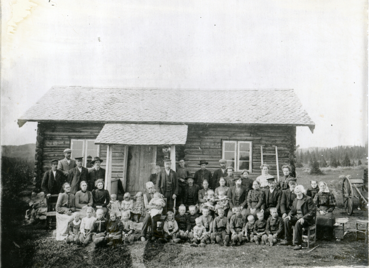 Folkemengde oppstilt framfor seterbua til Tamburgarden, Bagn, i samband med Ole O. Bang si reise til Amerika
