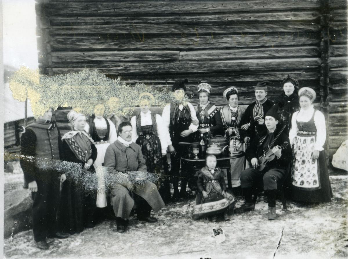 Brudepar i tradisjonelle brudedrakter frå Øvre Valdres, gjestar kledd i tradisjonelle høgtidsklede. Gjenstandar på bord, liten jente sittande på stol framfor bordet. Spelemann med fele