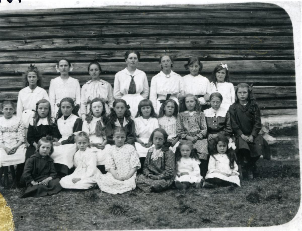 Gruppebilde av elever ved en søndagsskole. Oppstilt ved en tømmervegg