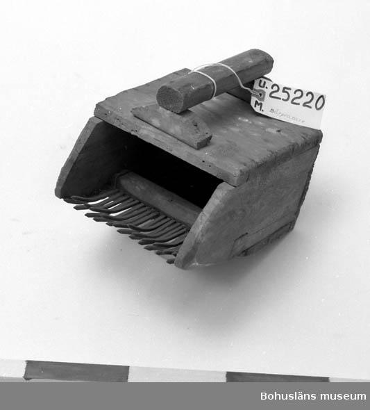 Gjord av en låda; text synlig på översidan. Handtag. I öppningens nederdel är det spikar i rad som skall göra att bären lossnar från sin kvist. Föremålet fanns i fastigheten Tegene i Forshälla vilken givaren köpte 1970.