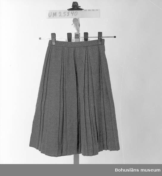 Grått tuskaftsvävt tyg i veckad kjol med 10 stycken permanentade dubbla motveck runt hela plagget. Smal linning med dragkedja och kapp i sidan. Svagt slitage ca 5 cm upp från nedre kanten från att kjolen lagts ner för att bli längre.  Etikett med vävd text: 55% terylene (Polyester fibre ICI) and 45 % wool. Storlek: 34. Viss pilling på tyget samt en ljusare fläck vid höfttrakten.  Berit Jacks var dotter till köpman Herbert Olsson f. d.1993, Uddevalla och Tyra Olsson. Berit Jacks, född 1 mars 1946, anställd som kanslist i kommunförvaltningen. Gift med givaren.  Tyra Olssons kläder UM25531 - UM25534 Berit Jacks kläder UM25535 - UM25546