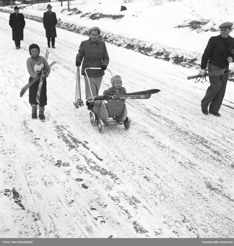 En stor serie bilder från Lasses Skidspel, en barnskidtävling med massor av glada barn och ett välfyllt prisbord. Troligen inspirerad av Svenska Skidspelen.