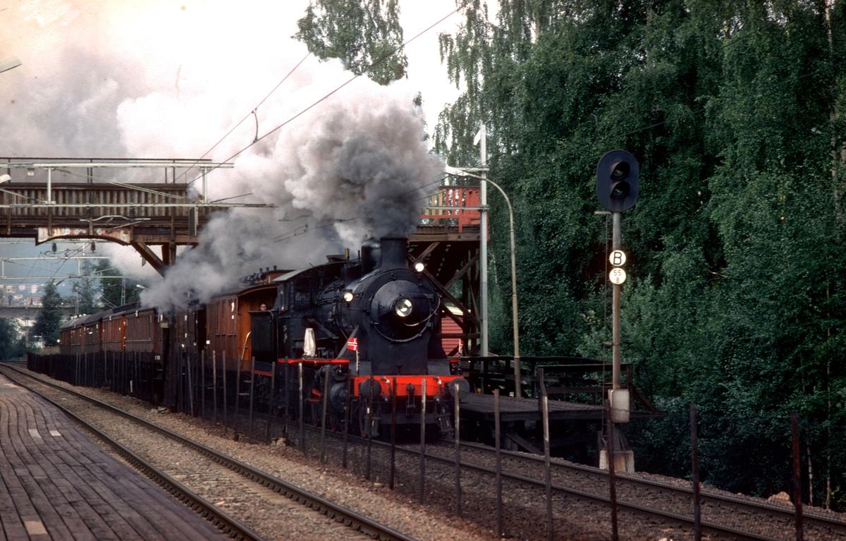Ekstratog i anledning jernbanens 125 års jubileum, Oslo - Eidsvoll passerer Høybråten holdeplass. Damplokomotiv 24b 236. Toget kjøres uriktig mellom Grorud og Lørenskog for å bli forbikjørt av annet tog.