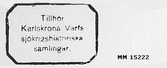"""Rektangulär stämpel med gummiplatta. Droppformat trågrepp. På gummiplattan bokstäverna: """"Tillhör Karlskrorna Varvs sjökrigshistoriska samlingar."""