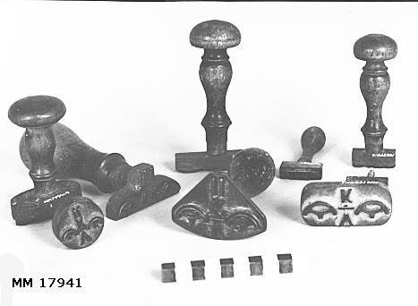 Stämplar av mässing, vissa gängade till träskaft. Olika format, samtliga försedda med kronostämpel, typ kattfot på vardera sida om bokstäverna. Spår av röd färg. MM 17941.6 : V K, nedanför II.
