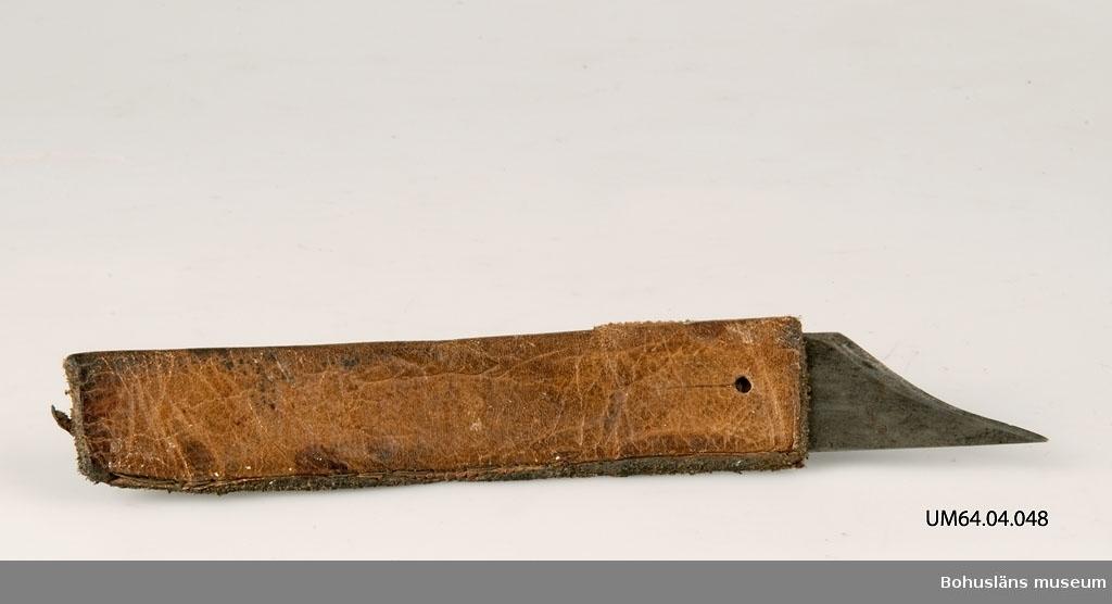 471 Tillverkningstid 1920-1940?  Knivblad med läderskaft, en f.d. knivslida, påträdd.  Lätt böjd, beläggningar på knivbladets bakre kortända.   Övriga uppgifter: Se UM64.04.001.  Ur punktnummerkatalogen 1958-1976: G. Arsenius, dödsbo Skomakariverkstad G. Arsenius, skomakeri U:a