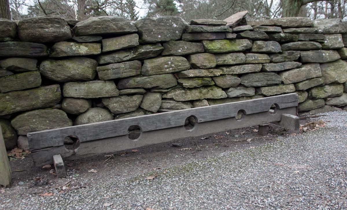 Straffstock av omålat trä med fem hål. Hasp och äldre lås. Kopia av straffstock NM.0025659 från Ukna sn, Småland.