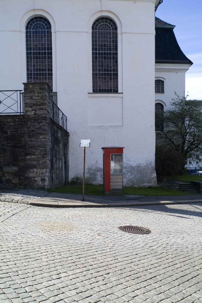 Telefonkiosken står ved Nykirken i Bergen, og er en av 100 vernede telefonkiosker i Norge. De røde telefonkioskene ble laget av hovedverkstedet til Telenor (Telegrafverket, Televerket). Målene er så å si uforandret.  Vi har dessverre ikke hatt kapasitet til å gjøre grundige mål av hver enkelt kiosk som er vernet.  Blant annet er vekten og høyden på døra endret fra tegningene til hovedverkstedet fra 1933. Målene fra 1933 var: Høyde 2500 mm + sokkel på ca 70 mm Grunnflate 1000x1000 mm. Vekt 850 kg. Mange av oss har minner knyttet til den lille røde bygningen. Historien om telefonkiosken er på mange måter historien om oss.  Derfor ble 100 av de røde telefonkioskene rundt om i landet vernet i 1997. Dette er en av dem.