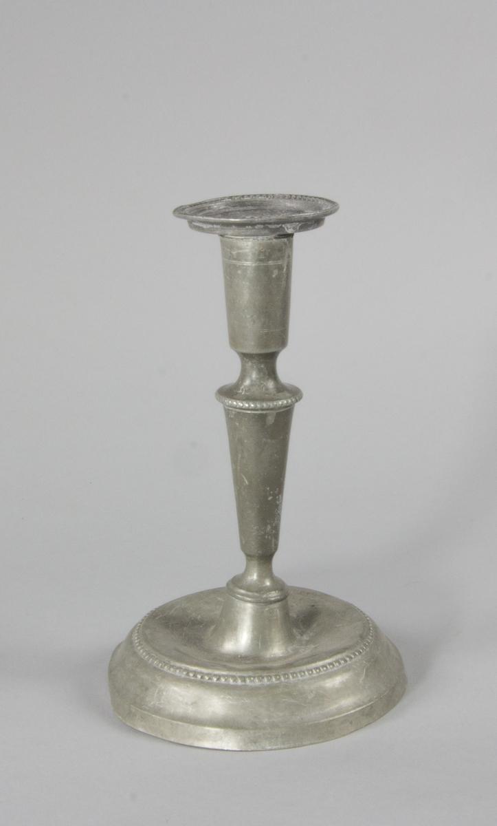 Ljusstake av tenn med pärldekor runt ljushållarens mynningskant och runt foten. Fyrstämplad och årsbokstav.