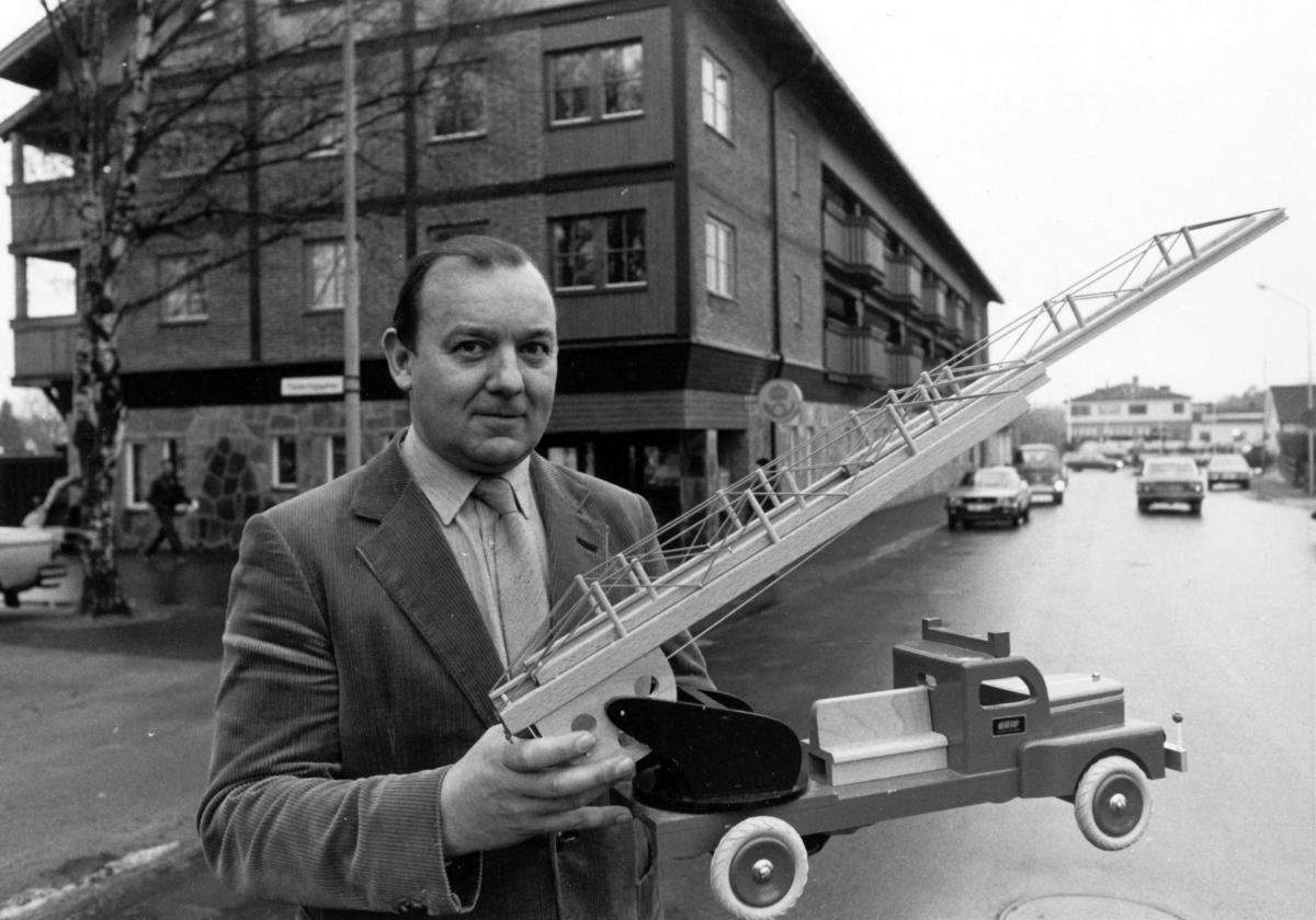 Samtidigt som det nya Postkontoret i Osby invigdes i november 1980 visades en leksaksutställning. Här håller postmästaren Östen Sjöquist i en brandbil från 1950-talet.