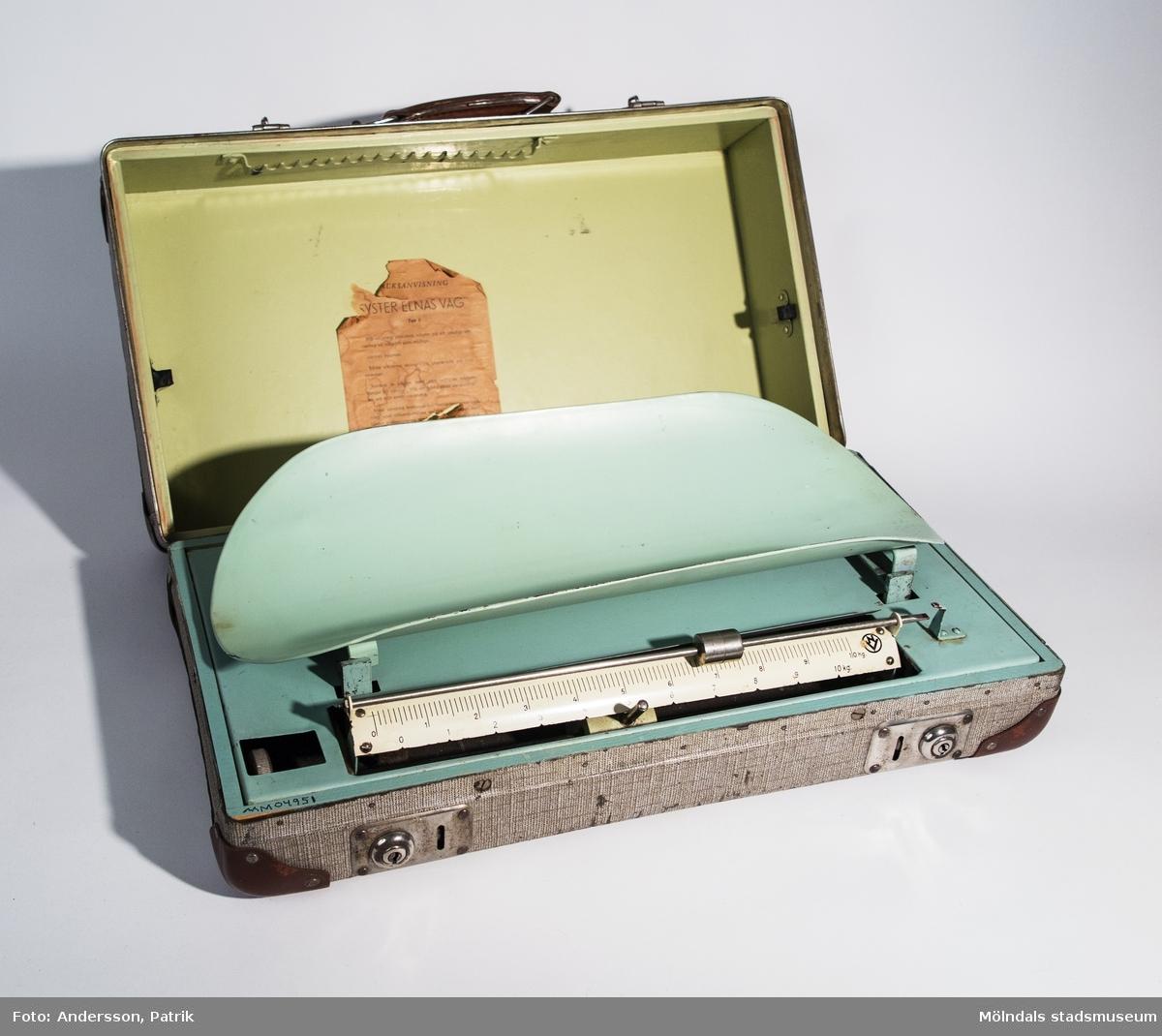 """Barnvågen - """"Syster Elnas Våg"""", tillverkad av Nynäshamns vågfabrik AB troligtvis någongång under 1940- eller 50-talet.Vågen är portabel för att sköterskor ska kunna ta med sig den vid hembesök. Den liknar en liten resväska. Väskan är smårutig som går i brunt och vitt. Hörnen är beklädda med brunt läder. Vid handtaget som också är av brunt läder sitter en blå liten plåtskylt med texten: """"AXEL KISTNER Syster Elnas Våg STOCKHOLM - GÖTEBORG"""". Man öppnar och stänger väskan med två blanka metallbeslag.När man öppnar väskan sitter vågskålen med dess underrede fast på väskans insida. Vågskålen och dess underrede är i turkos plåt. Mätstickan är vit. Lockets insida är klädd i ljusgrön plåt. Där finns ett mycket slitet och gulnat papper fastklistrat. På pappret finns bruksanvisningen för vågen tryckt med svart text:""""BRUKSANVISNINGSYSTER ELNAS VÅGTyp 2Vid vägning placeras vågen på ett stadigt underlag så vågrätt som möjligt.Locket öppnas.Båda vikterna skola vara placerade på nollstrecket.Justera in vågen med den refflade muttern längst till vänster, tills de båda röda siktpunkterna stå mitt emot varandra.Med särskild konstruerad fastspänningsanordning som tillhandahålles av oss … vågen med fördel transporteras … såväl cykel som sparkstötting.Är väskan ordentligt stängd, är vågen oöm för transporter.NYNÄSHAMNS VÅGFABRIK ABNYNÄSHAMN""""MåttVäska - Längd: 535 mm, Bredd: 295 mm, Djup: 154 mmVågskålens underrede - Längd: 500 mm, Bredd: 260 mmVågskål - Längd: 490 mm, Bredd: 214 mm"""