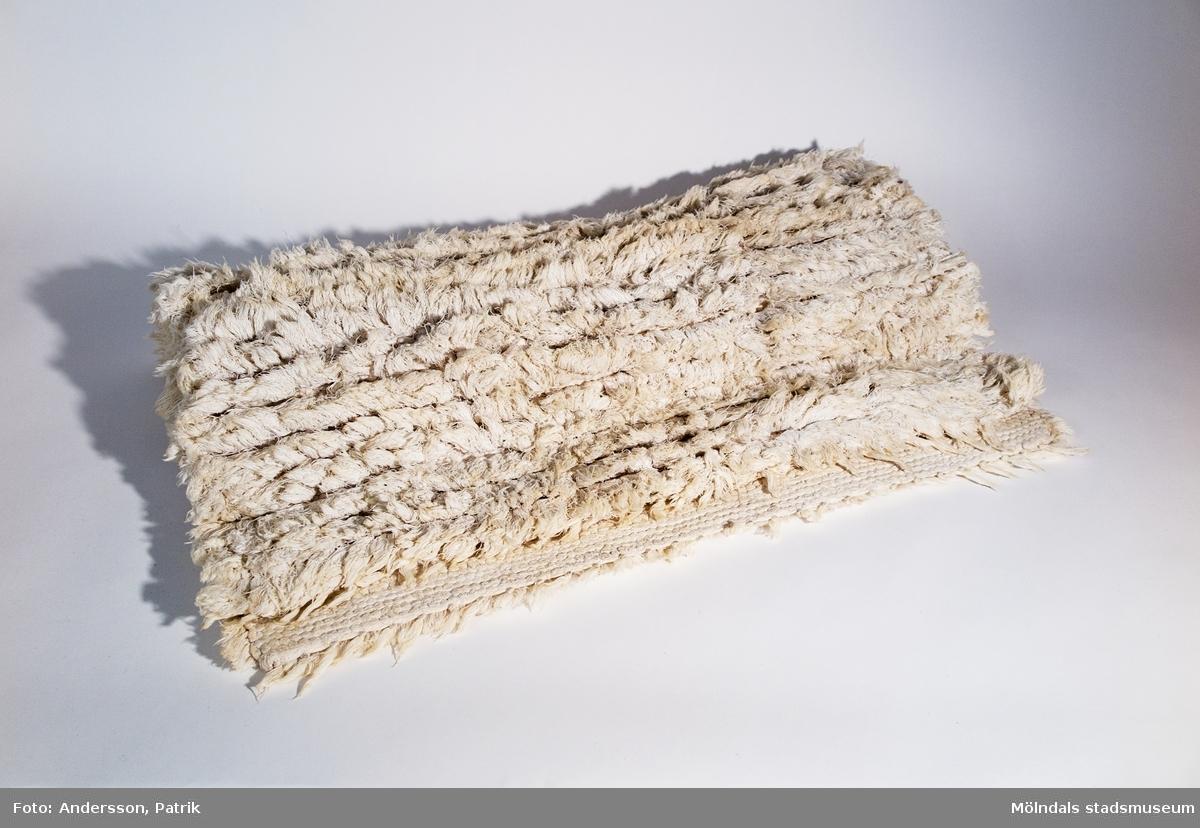Matta i vit bomullsrya vävd med inslag frånn lakans-varp, av textilkonstnärinnan Märta Östlund.   Märta Östlund föddes på Flatön i Bohuslän 1926. 1940 reste Märta till Göteborg för att söka arbete och utbildning. I slutet av andra världskrigen var Märta färdigutbildad vävlärare och i samband med det startade hon även en privat vävskola.