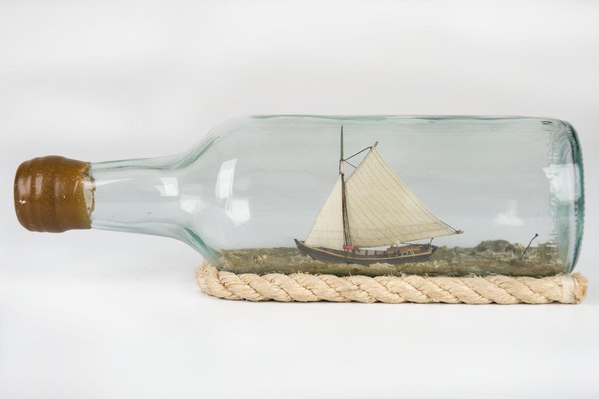 Flaskskeppsmodell av sandkil under segel med jolle på släp. Flaskan vilar på skrå av otjärat rep.