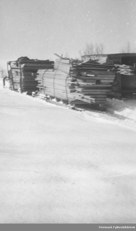 Gjenreisningen av Finnmark rett etter frigjøringen. Frakt av utstyr og materiale fra Alta til Kautokeino. Beltevognstraktor frakter store lass med tømmerbord. På noen av bildene ser vi føreren av traktoren og andre arbeidsfolk. Området er snødekt og flatt, typisk for Finnmarksvidda: serien inneholder bildene: 06002-052, 06002-053, 06002-055, 06002-056, 06002-057, 06002-058. Ca.1946-50.