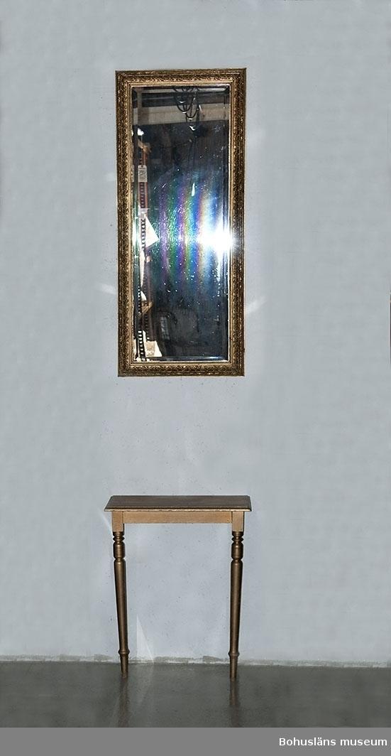 Bord använt ihop med spegel UM025943, ehuru de ej ursprungligen hört ihop.  En kant försedd med två svarvade framben. Slät skiva med profilerad kant framtill och i sidorna. Historik se UM025943