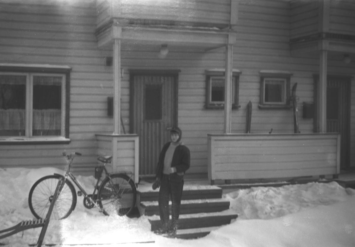 En ukjent, ung person står ved inngangspartiet til et hus. Både en spark og en sykkel står i snøen. Stedet er ukjent.