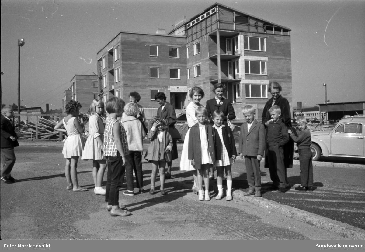 Skolstart på Sankt Olofsskolan. Förväntansfulla barn och mammor samlas utanför skolan. I bakgrunden syns kvarteret Tegen där bygget av det så kallade Långholmen pågår.
