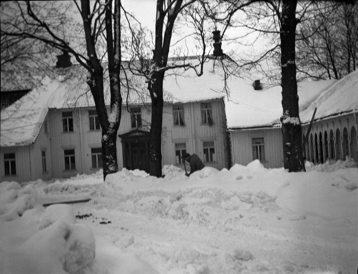 Fotoarkivet etter Gunnar Knudsen. En mann som måker snø foran Borgestad gård.