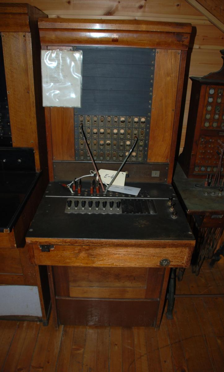 Sentralbord med koblingspanel der telefonsamtaler kobles ved hjelp av kabler med plugg. Står på gulvet og betjenes av en person. Kapasitet 40 linjer, for magnettelefon.