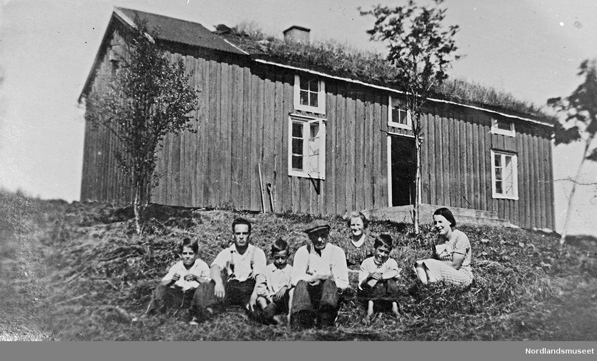 3 menn, 2 kvinner og 2 barn som sitter på marken utenfor et hus.