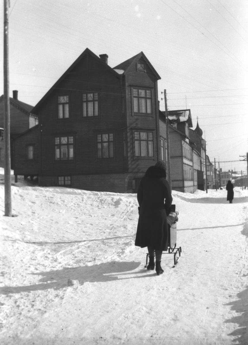 En dame går bortover Havnegata med barnevogn en vinterdag. Sellstrømgården er den nærmeste bygningen.
