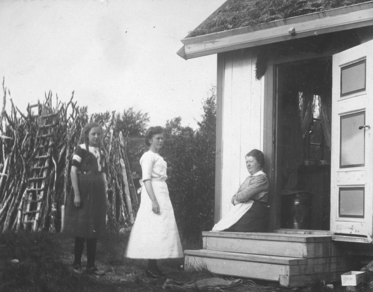 En dame sitter på trappen utenfor hytta. To jenter står ved siden av. Den ene har lys sid kjole, og den yngste fletter og mørk kjole. Bak dem er det et råveskjul.