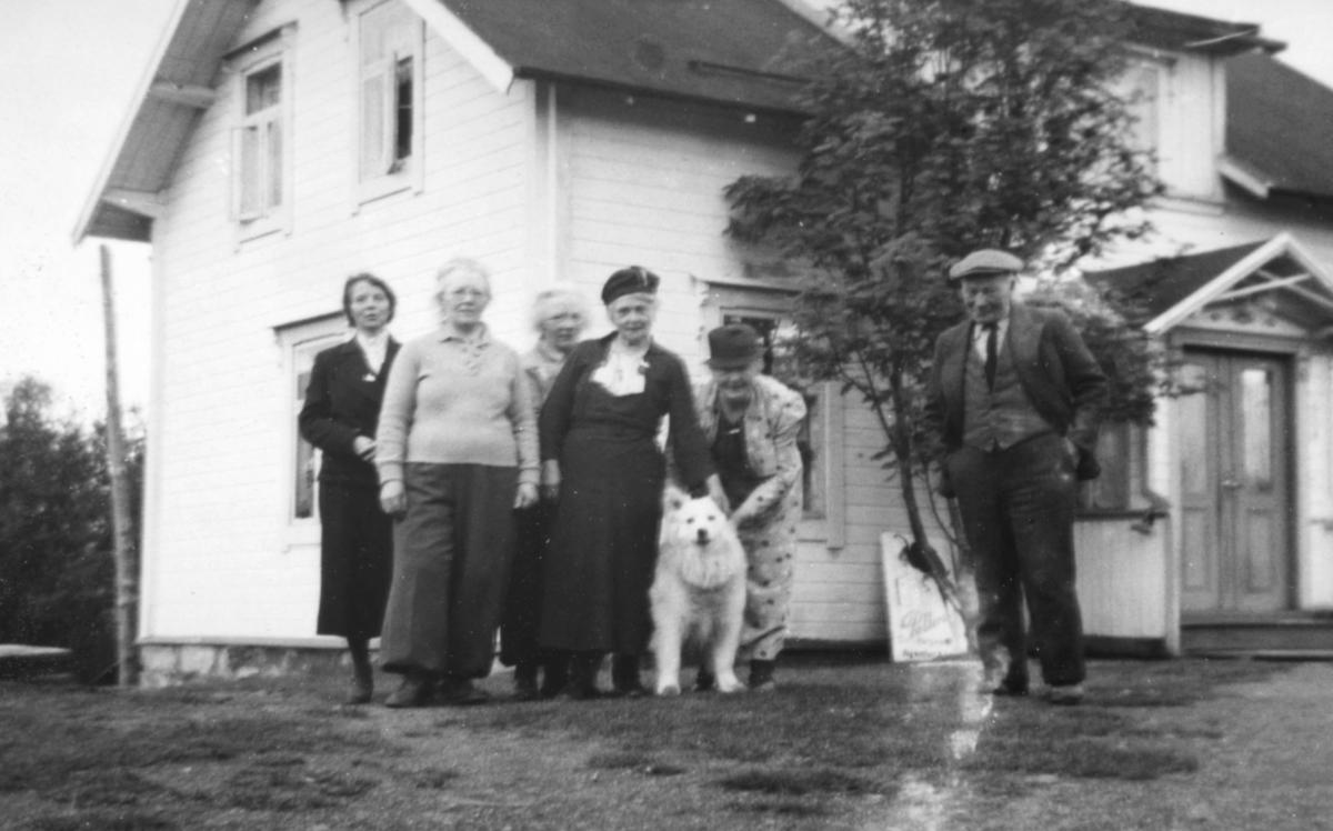 Fem damer og en mann + en hund står foran en bygning.