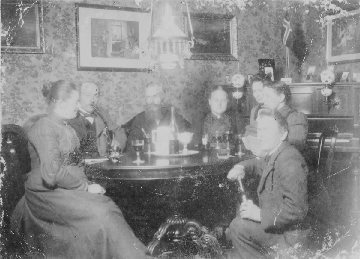 """Gruppebilde av  7 kvinner og menn rundt et bord i en dagligstue. Fra venstre Karoline Ohlsen og videre hennes mann, handelsmann Karl Oluf Ohlsen som opprinnelig kom fra Namdalen. På bordet står det glass med vin. Fru Karoline hadde svenske foreldre (Lindberg). Paret hadde forretning i Nyborg, Nesseby.  Nyborg Handelssted ble grunnlagt av Bergitte og Andreas Brodtkorb. Handelsstedet Nesseby ble bebygd omkring 1850 og hadde et stort våningshus som var oppført av byggmester Sveve som også bygde kirken i Nesseby og kirke og rådhus i Vadsø. I 1865 ble Nyborg overtatt av datter av Bergitte og Andreas Brodtkorb. Jensine Freddrikke Johanne Brodtkorb og hennes mann Otto Andreas Pleym jr. som solgte brennevin og hadde store salg på Varangermarkedet i Karlebotn.  I folketellingen av 1875 bodde det 13 personer i Nyborg. I 1880 ble virksomheten i Nyborg endret til firmanavnet Brødrene Pleym. Nyborg var viden kjent for sin gjestfrihet på denne tiden og det kom gjester fra Vardø, Vadsø, Nesseby og Tana (nå Tana-Polmak) med sleder til Nyborg ved jul- og påsketider. Så var det dagen lang festeligheter med spill, dans, komedie show og mer. I en gammel bok skrevet av Nils A. Ytreberg, """"Handelssteder i Finnmark"""" - kan man se bilder som viser et hageselskap med krokettspill (side 272) fotografert hos Pleym, Nyborg. Her finnes det også et familiebilde av familien Otto Pleym senior, tatt på trappen til Nyborg."""