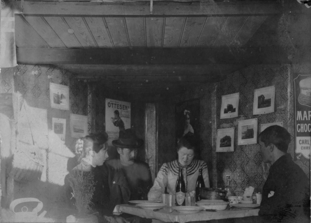 Blåsenborg 18. september 1905. To damer og to menn sitter ved et bord inne i en hytte. På veggene er det plakater og bilder. På bordet står flasker og tallerkner.